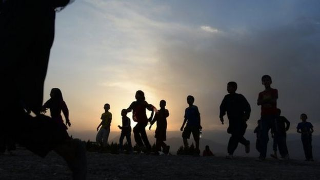 Afghan children run to see the largest Afghan flag after an inauguration ceremony at Wazir Akbar Khan hill in Kabul on September 10, 2014.