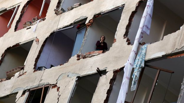 A woman looks out of a ruined building in Diyarbakir, 4 November
