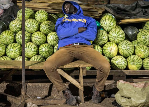 A trader sleeps by his melon stall in Kampala, Uganda - Wednesday 8 April 2020