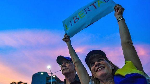 Manifestante con cartel en Venezuela.