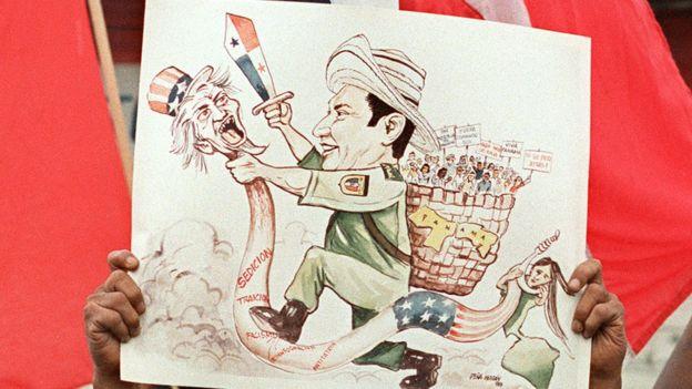 Pancarta con la caricatura de Manuel Noriega golpeando al Tío Sam.
