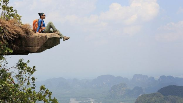 A young woman enjoying the view at a mountain peak in Asia