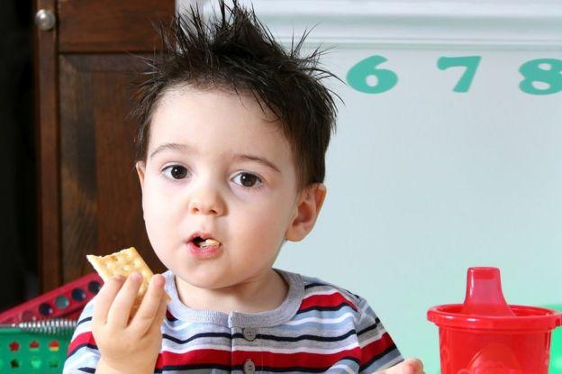 Niño comiendo una galleta.
