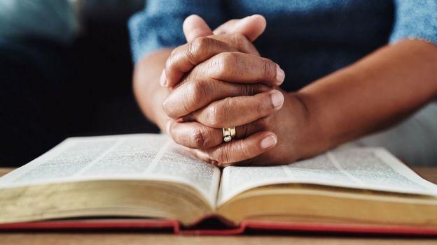 Mulher com as mãos entrelaçadas reza sobre uma Bíblia