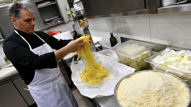 Un chef prepara la pasta con salsa Alfredo