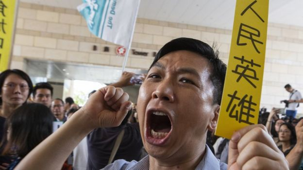 "A pro-Democracy activist holds a piece of yellow paper with a slogan in Chinese saying ""People""s Hero"""