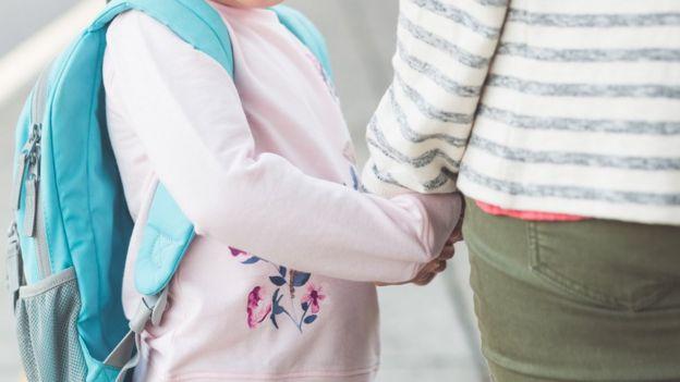 Una niña tomada de la mano de una mujer