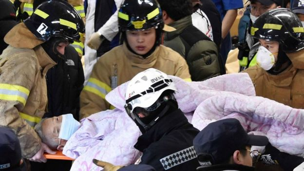 Rescue workers remove a survivor from a hospital fire on 26 January 2018 in Miryang, South Korea - handout picture provided by Kim Gu Yeon/Gyeongnam Domin Ilbo