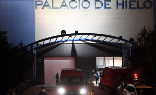 Police and military wearing protective suits stand as a van leaves the Palacio de Hielo shopping mall where an ice rink was turned into a temporary morgue on March 23, 2020