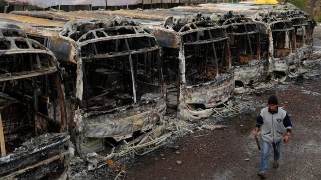 """man walks past buses burned during a protest after Bolivia""""s President Evo Morales announced on Sunday that he was resigning, in La Paz, Bolivia November 11, 2019."""