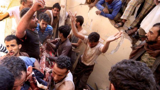 يمنيون ينتشلون جثة من تحت أنقاض في صنعاء إثر غارة شنتها قوات التحالف بقيادة السعودية (صورة أرشيفية)