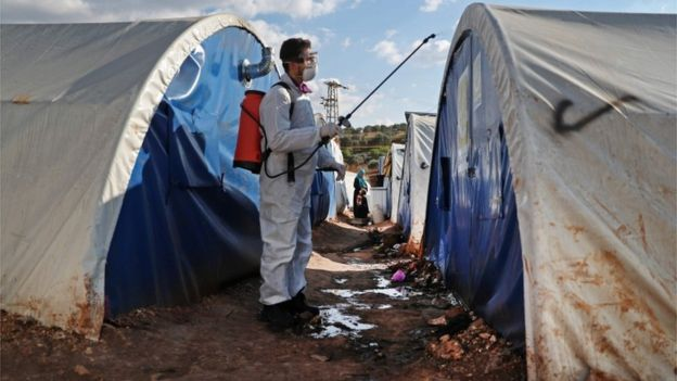 A member of the Syrian Violet NGO disinfects tents at a camp for displaced people in Kafr Jalis village, north of Idlib city, on March 21, 2020