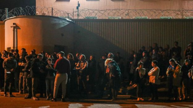 People wait for detained protesters to leave a temporary detention facility