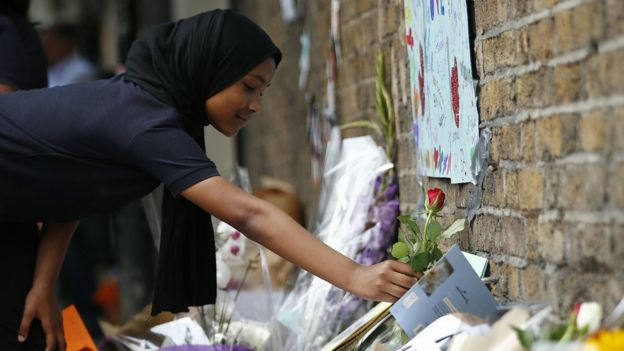 Children lay flowers in tribute to the victims of a van attack in the Finsbury Park area of north London.