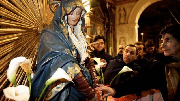 Mujer italiana le reza a la Virgen