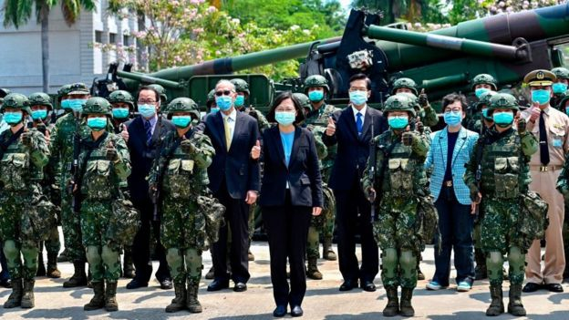 Taiwan President Tsai Ing-wen (C), seen wearing a face mask amid the COVID-19 coronavirus pandemic alongside soldiers and officials