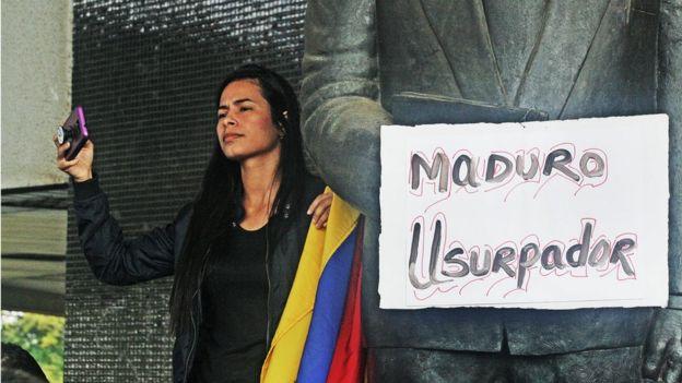 Mulher segura cartaz que diz: 'Maduro usurpador'