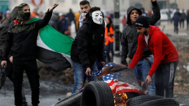 Palestinian protesters burn a US flag during a protest against Donald Trump's peace plan in the occupied West Bank (11 February 2020)