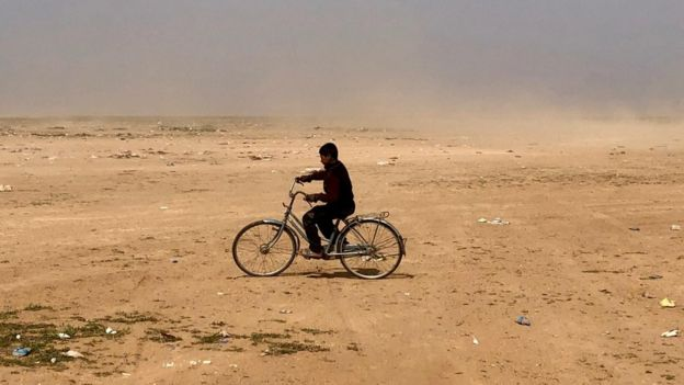 A boy plays with a bicycle