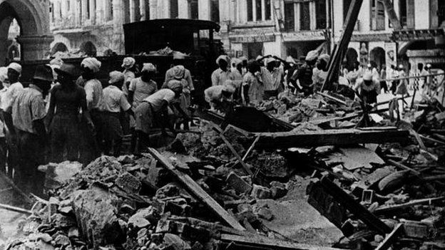 Workers in Singapore clear debris following bombing by Japan