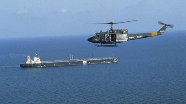 Зеленый вертолет с открытой дверью и видимыми солдатами летит над танкером с надписью, напоминающей японский флаг, - на хвосте вертолета стоит надпись NAVY и эмблема ВВС США «Рундель».