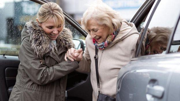 Una mujer joven ayudando a otra más mayor a salir del auto.