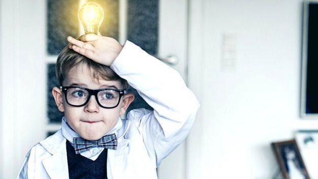 Un niño sostiene una bombilla sobre su cabeza.