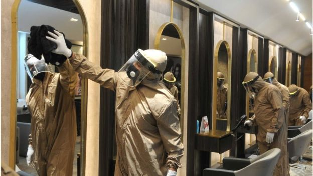 A salon is disinfected by workers in PPE suits before reopening 2 June 2020 in Chandigarh