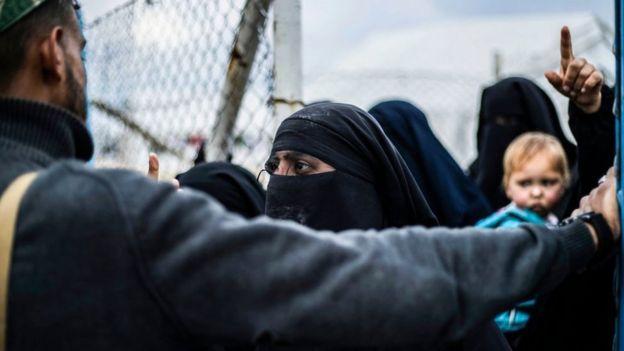 Miembro de las FDS en frente de una mujer en el campo de al-Hol.