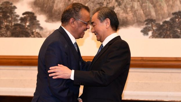 Tedros Adhanom, Director General of the World Health Organization, (L) shakes hands with Chinese State Councilor and Foreign Minister Wang Yi