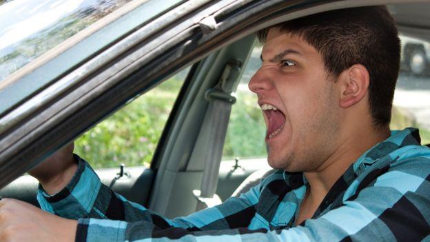 Hombre conduciendo un auto e insultando