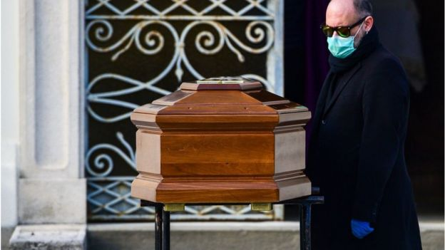 3月20日,一名男子戴着口罩在伦巴第附近贝加莫附近的塞里泰(Seriate)封闭公墓举行的葬礼中(他站在母亲的棺材旁)