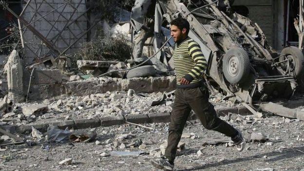 Un hombre corriendo después de un ataque en Guta Oriental.