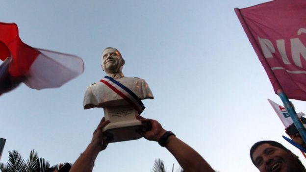 Un busto de Augusto Pinochet es alzado por seguidores del gobierno militar durante una celebración por la victoria de Piñera.