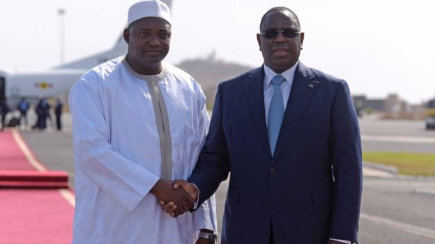 Senegal's President Macky Sall (R) shakes hands with Adama Barrow prior to leaving the Senegalese capital Dakar for The Gambia on January 26, 2017