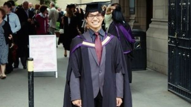 Reynhard Sinaga posing for a picture in his graduation gown