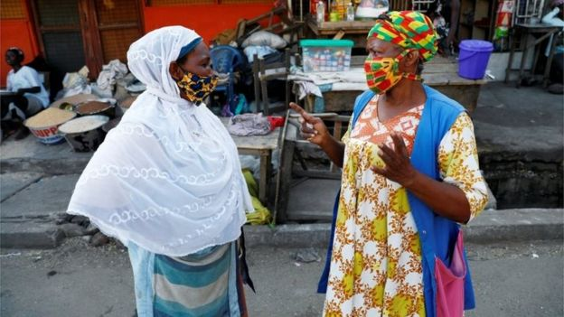 Women wearing face masks chat at the Nima market as Ghana lifts partial lockdown amid the spread of the coronavirus disease (COVID-19), in Accra, Ghana April 20, 202