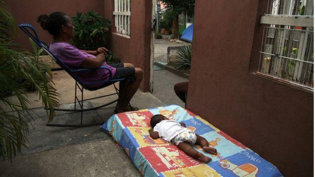 Mujer en sillón sentada, bebé sobre colchón