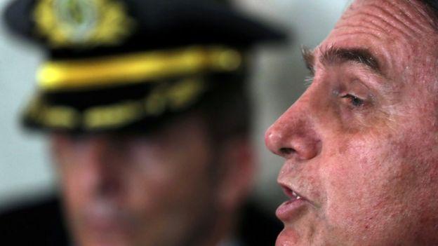 Bolsonaro aparece de perfil e falando, com homem fardado no plano de fundo