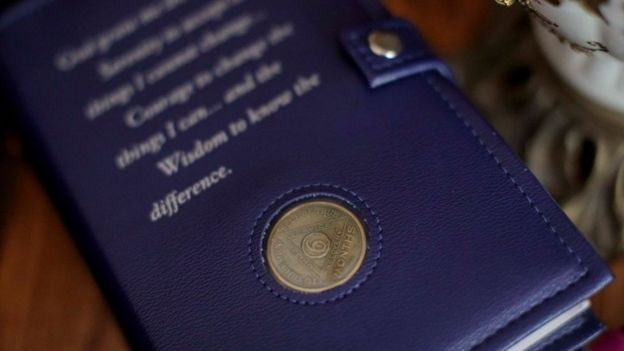 A copy of AA's Big Book with a leather cover and a six month sobriety coin