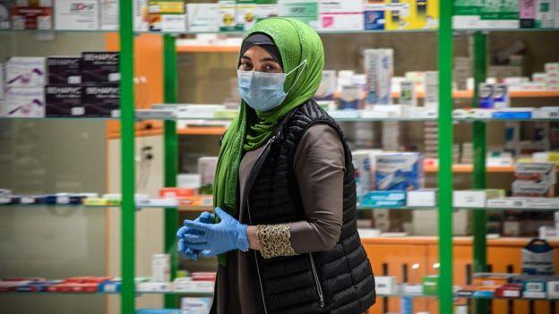 面罩的女人走过莫斯科药房