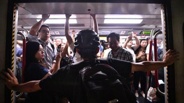 протестующий удерживает двери