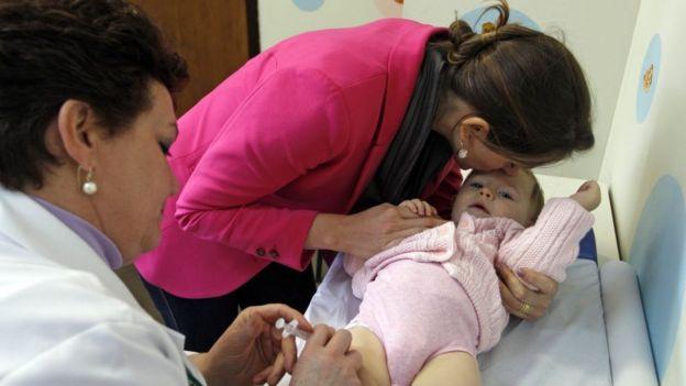 Criança de colo recebendo vacina
