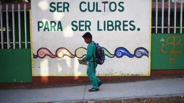 Un niño mexicano camina frente un cartel: