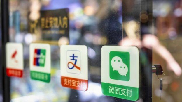 Etiquetas de WeChat y de otras apps de pago en la puerta de un comercio.