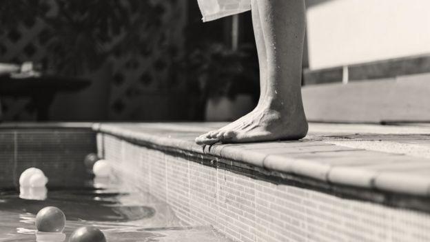 Imagem mostra pés de homem na borda de uma piscina