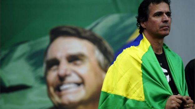 Militante em convenção partidária com foto de Jair Bolsonaro ao fundo
