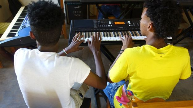Two people playing the electric piano
