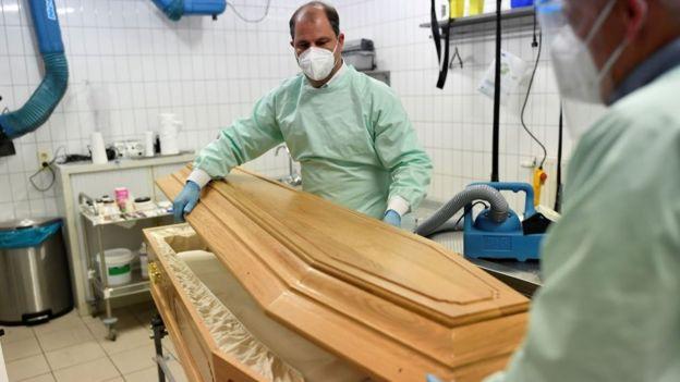 Dois homens de máscara segurando um caixão
