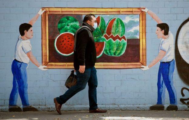 Hombre con mascarilla pasando por delante de un mural en Ciudad de México el 20 de abril de 2020.